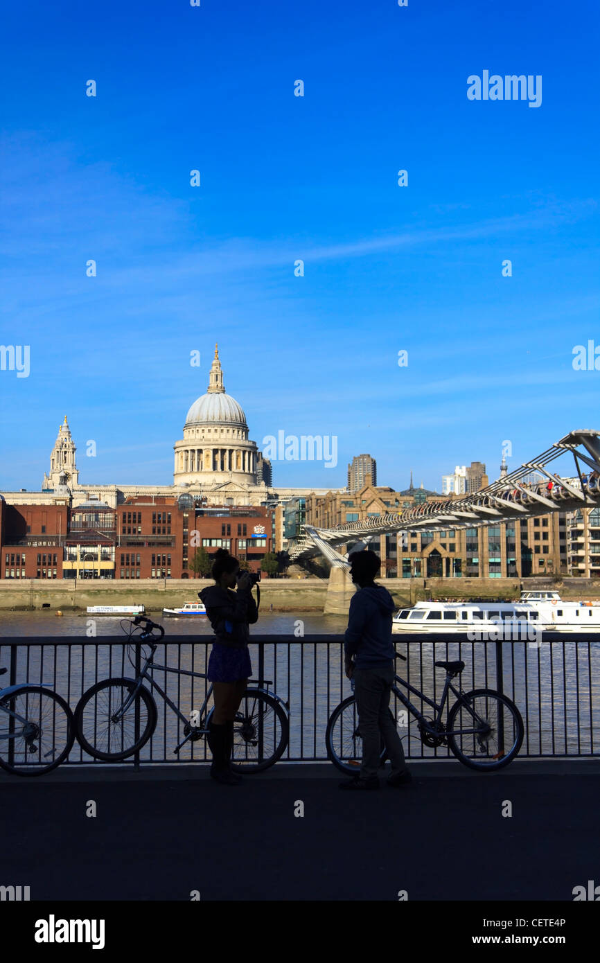 A young couple take photos across the river Thames in front of St.Paul's Cathedral in London, UK. Stock Photo