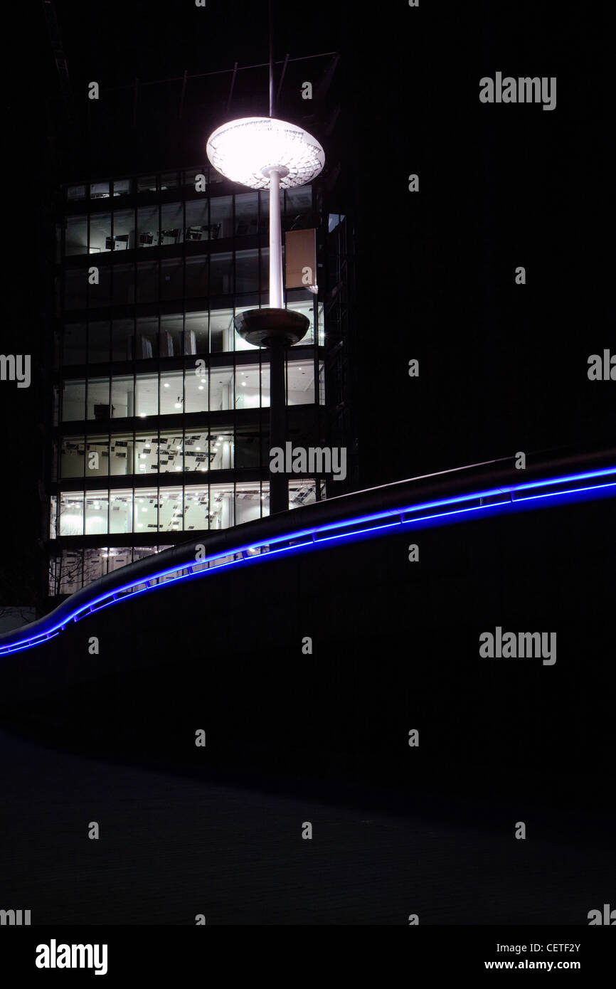 A blue neon light and street lamp outside London City Hall at night. - Stock Image