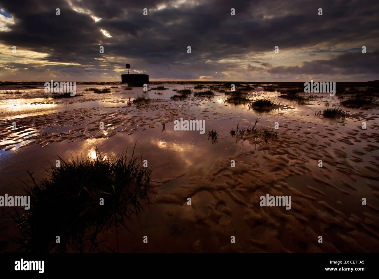 Dark skies over a tide groyne at low tide in Fleetwood. - Stock Image