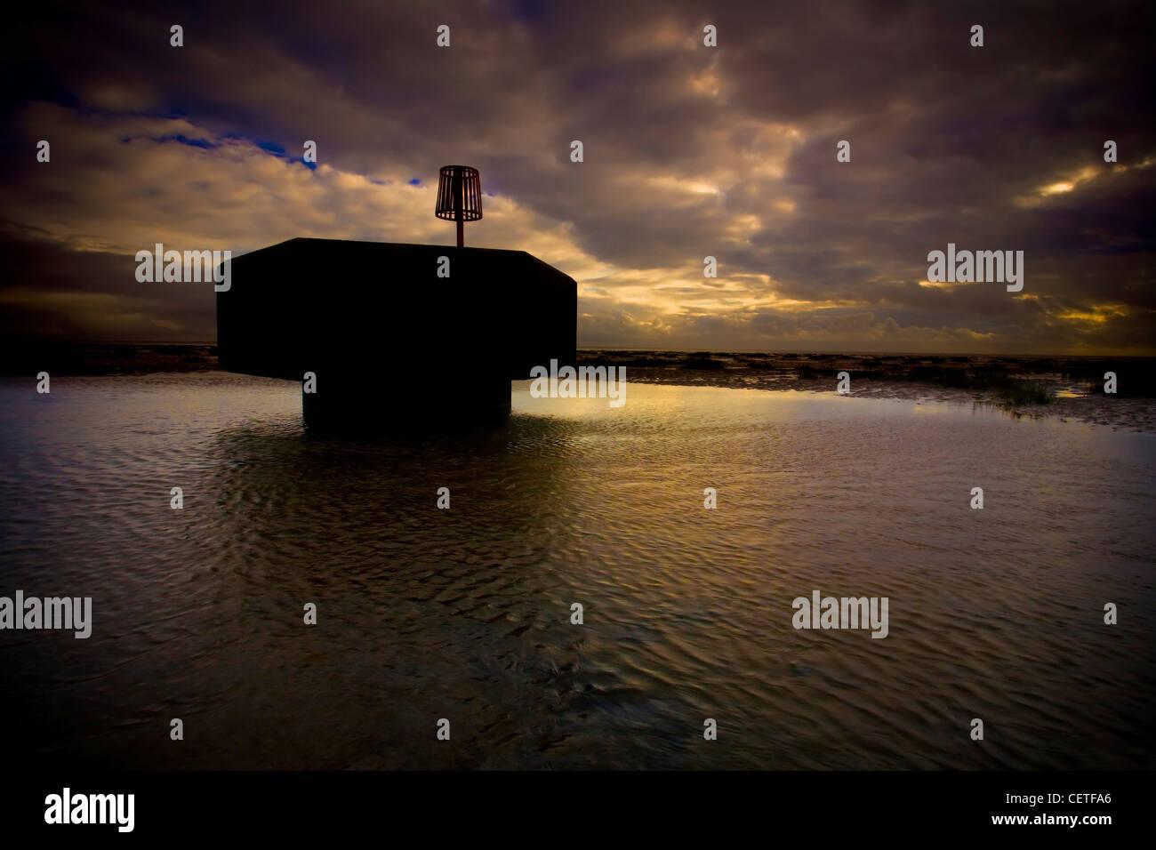 Dark skies over a tide groyne at high tide in Fleetwood. - Stock Image