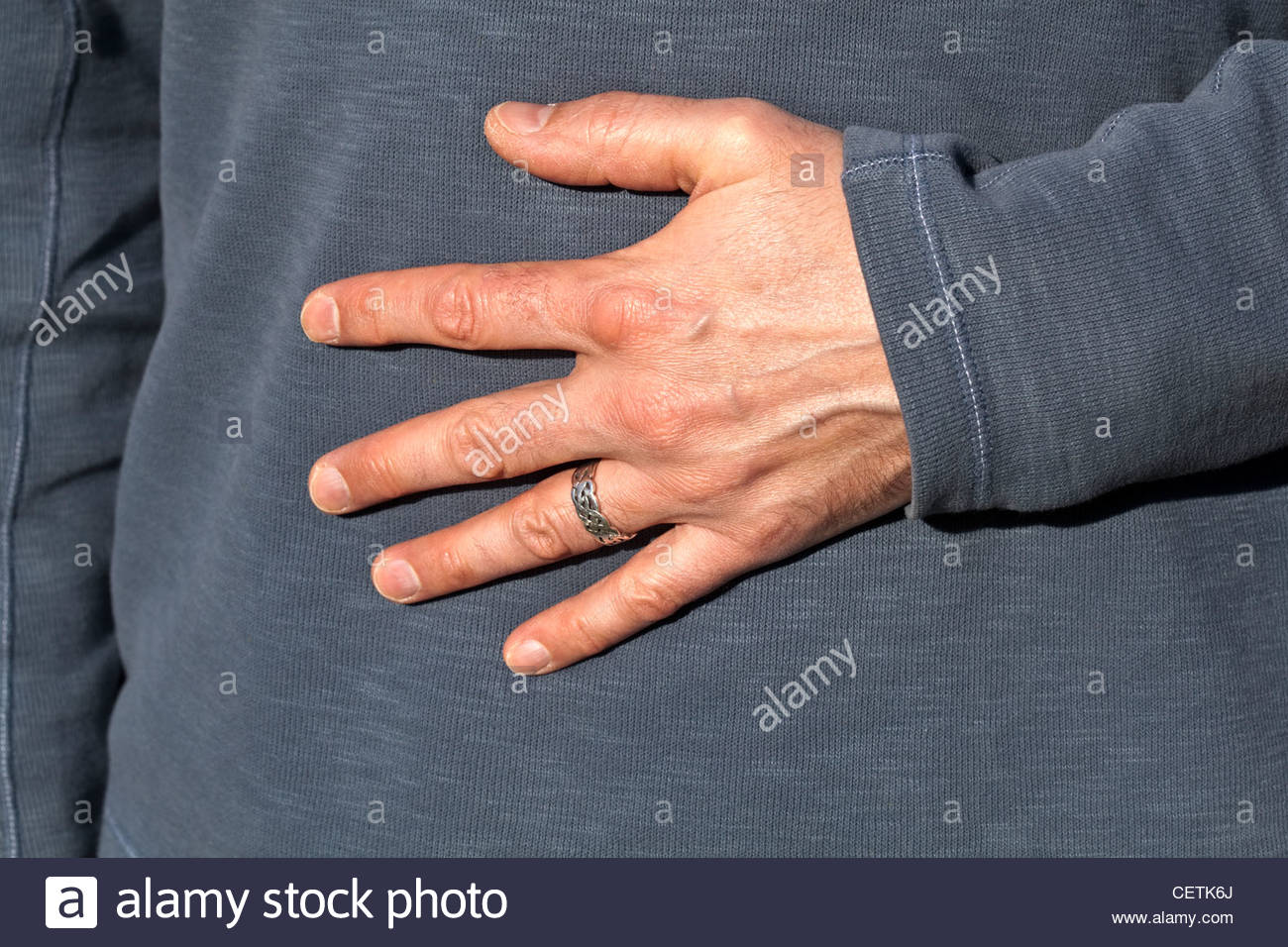 Mans hand wearing silver wedding ring on finger Stock Photo