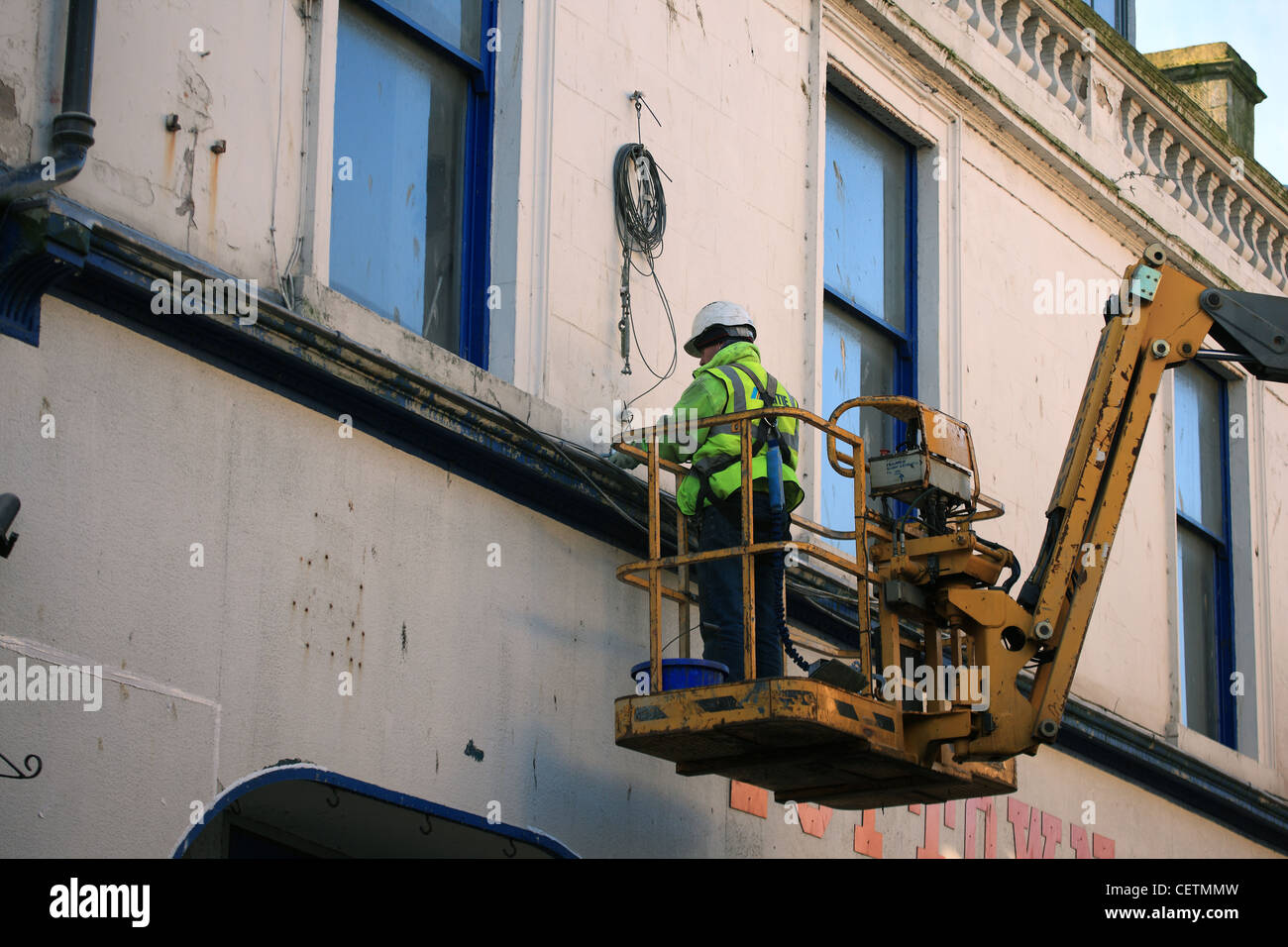 Workman wearing safety harness and hard hat on a crane hoist in the Scottish town of Ayr - Stock Image