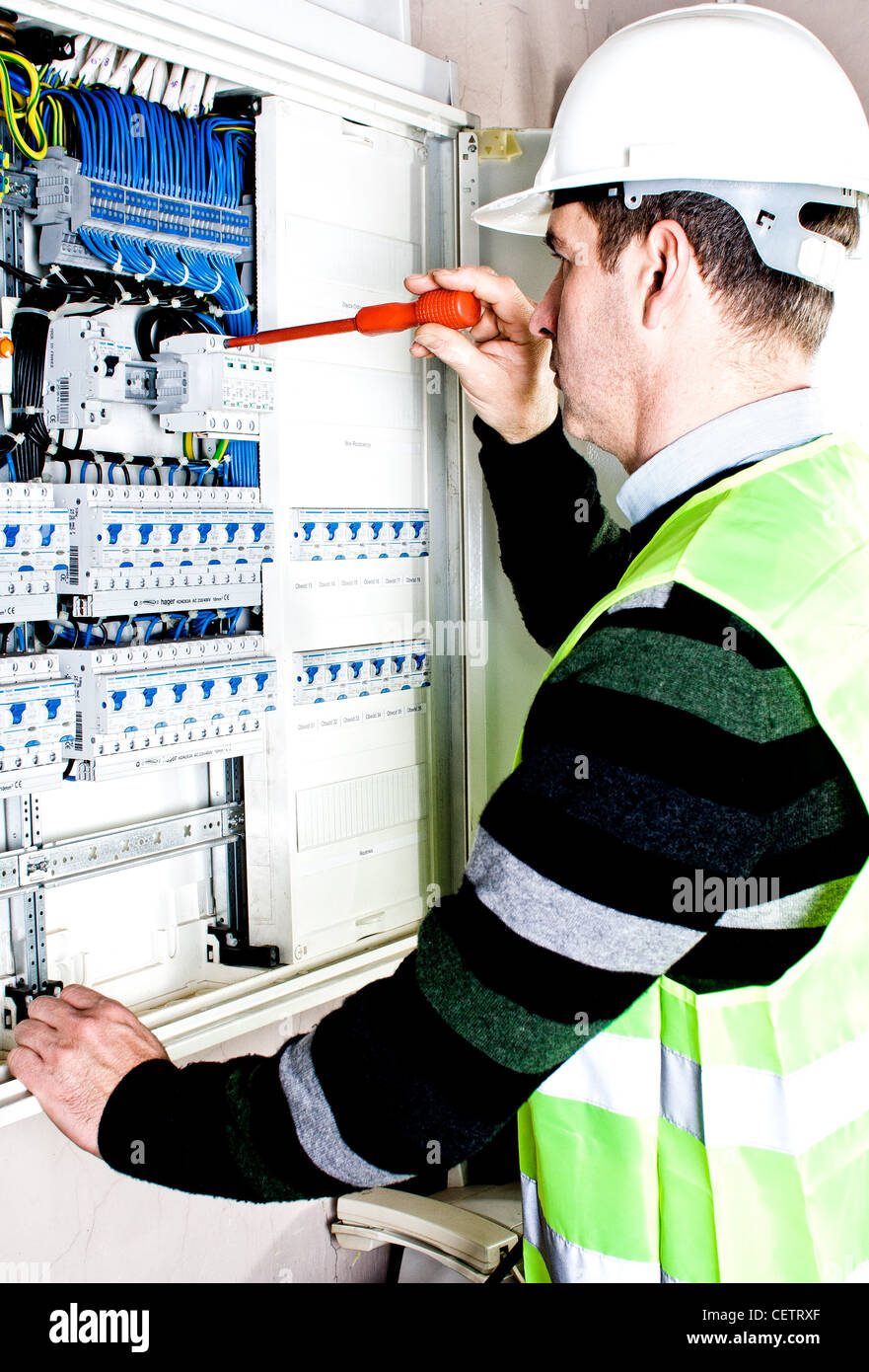 Electrician checking a fuse box - Stock Image