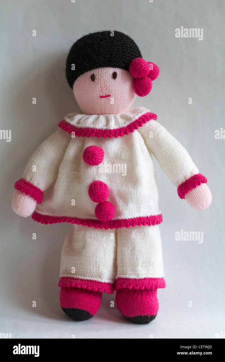 knitted doll - clown in pink and white outfit isolated on white background - Stock Image