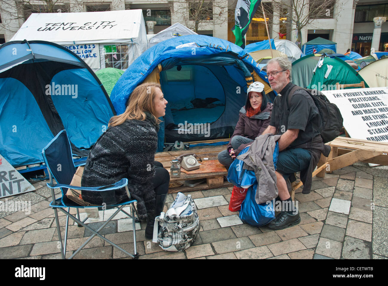 Occupy London St Pauls. Visitors and protesters sit in front of tents discussing the effects of the economic situation - Stock Image