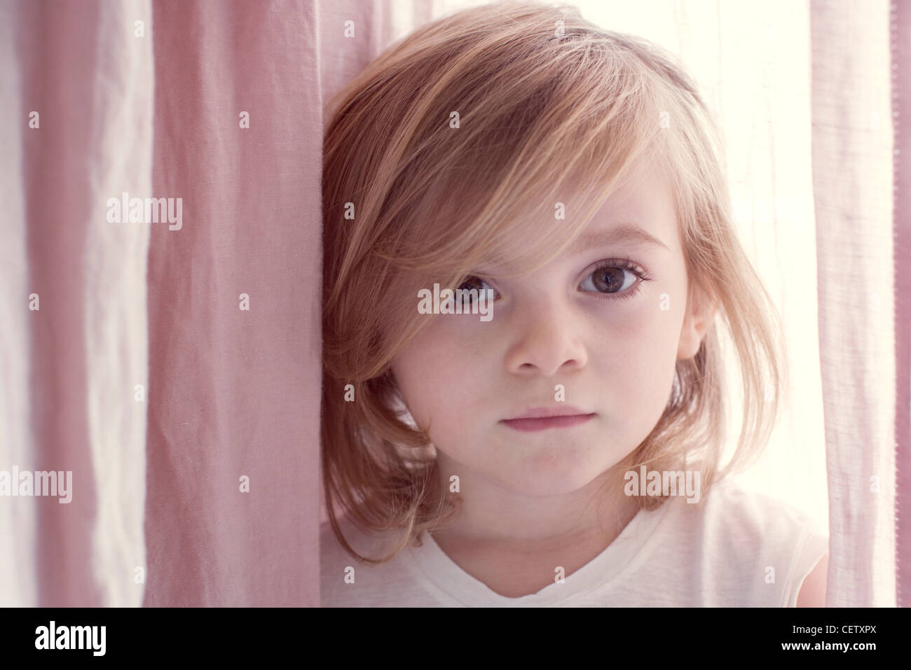 Little girly looking shyly at camera, portrait - Stock Image