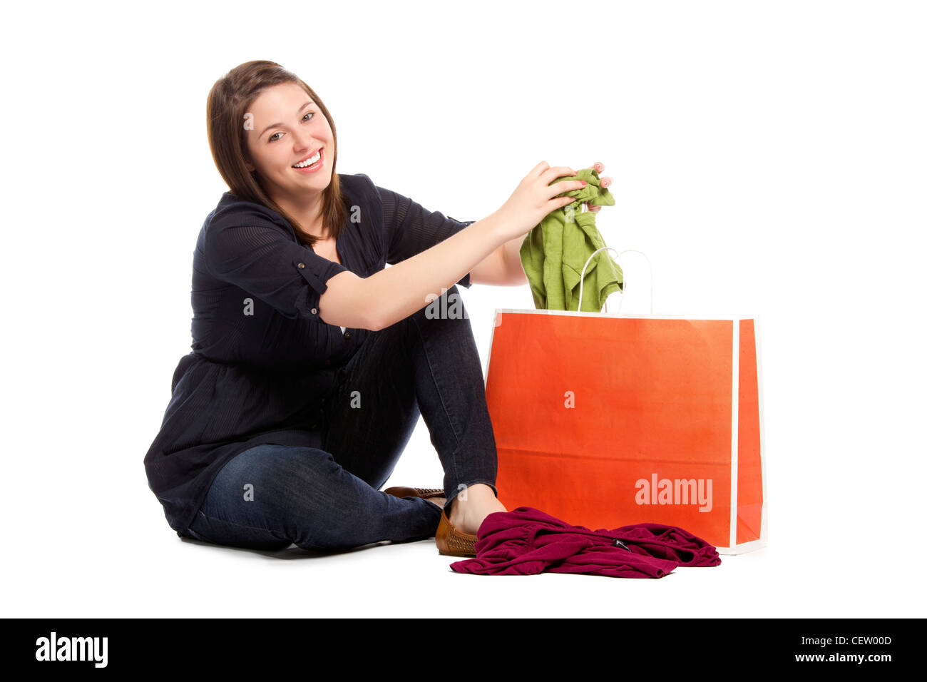 Young woman displaying her new green top bought during sale - White background  - Stock Image
