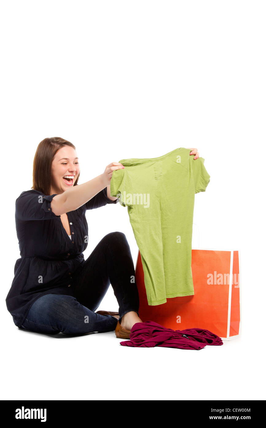 Portrait of young woman checking her green top bought during sale - Isolated  - Stock Image