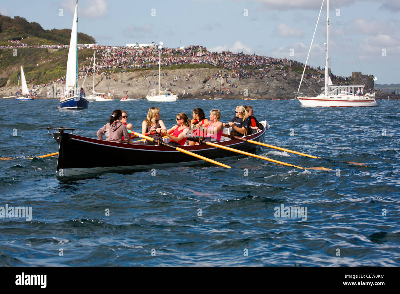 A ladies team of gig rowers, row a pilot gig ashore after a regatta - Stock Image