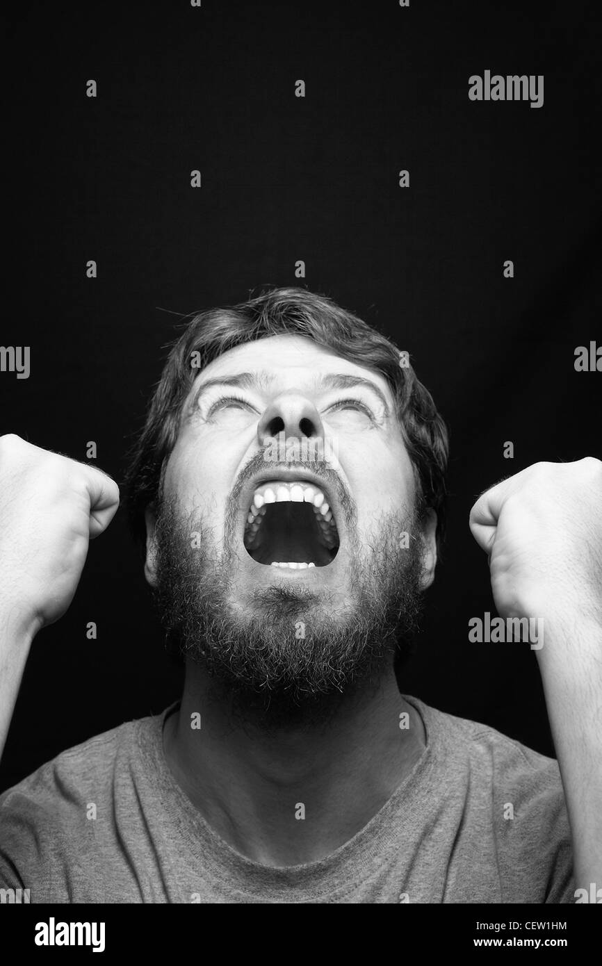 Scream of angry rebel man over black - Stock Image