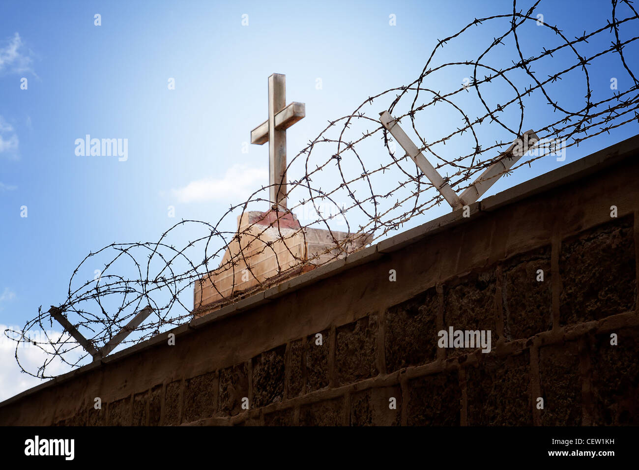War and religion concept - Cross and barbed wire over blue sky - Stock Image