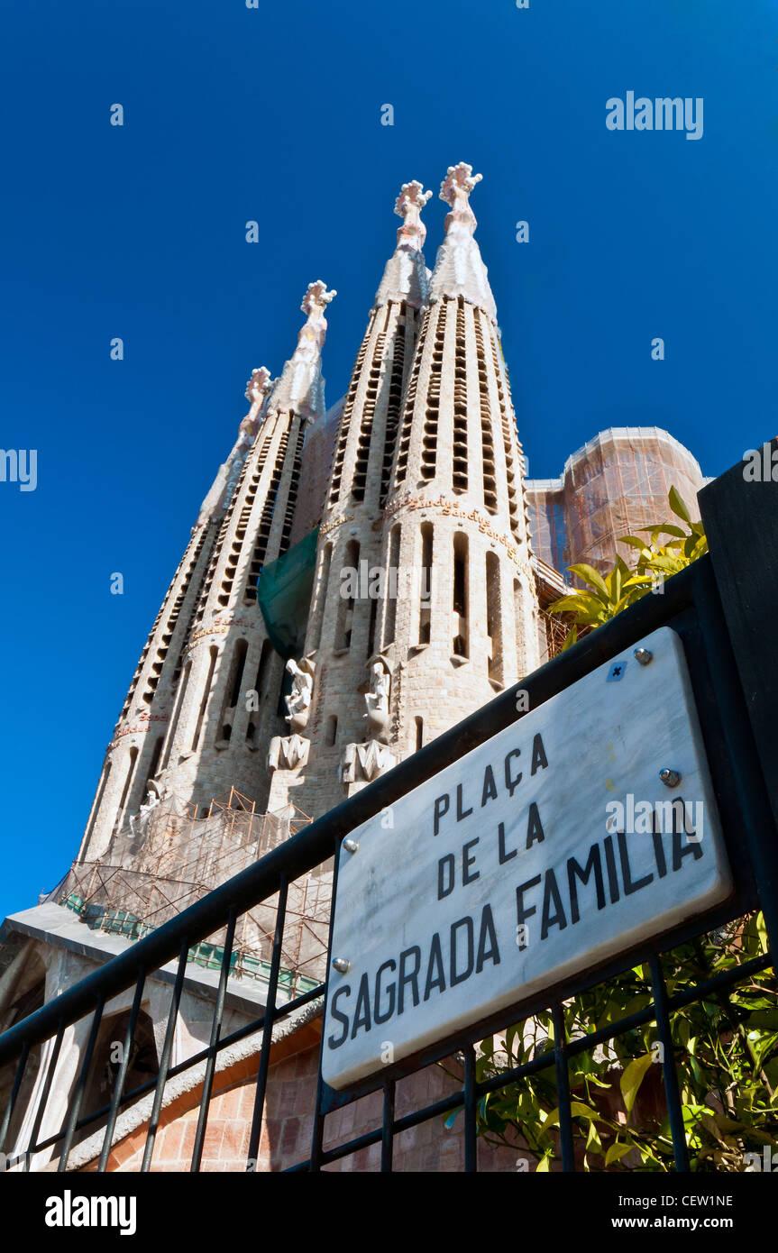 Day view of the Passion facade with placa de la sagrada familia sign, Sagrada Família church, Barcelona, Catalonia, - Stock Image