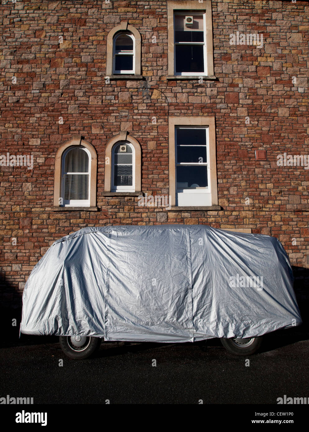 VW camper van with weather cover outside Victorian house - Stock Image
