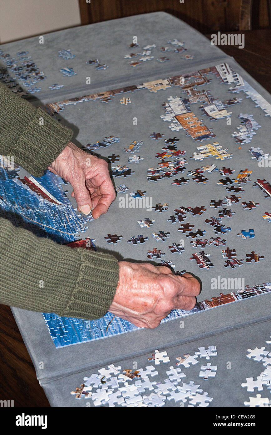 Hands of a Lady doing a Jigsaw Puzzle - Stock Image