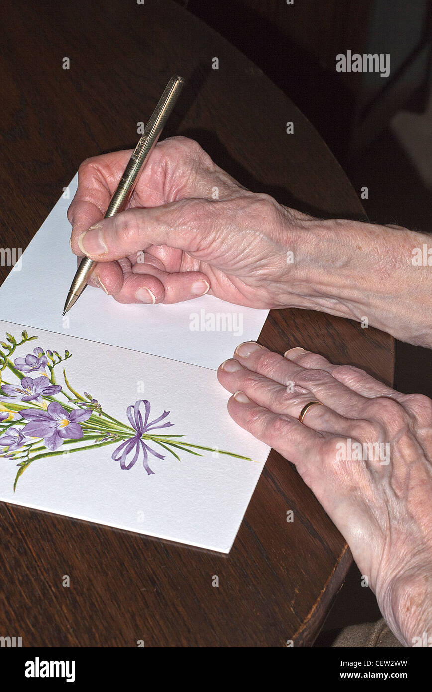 Hands of a Lady Writing a Greeting Card, UK. - Stock Image