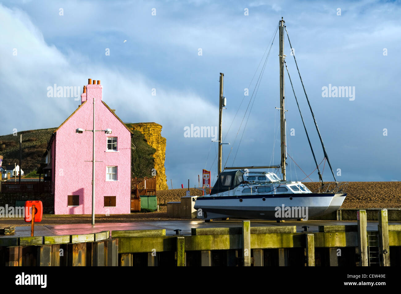 Colourful scene of house, cliffs and boat taken at West Bay harbour near Bridport, Dorset, uk after a storm in winter Stock Photo
