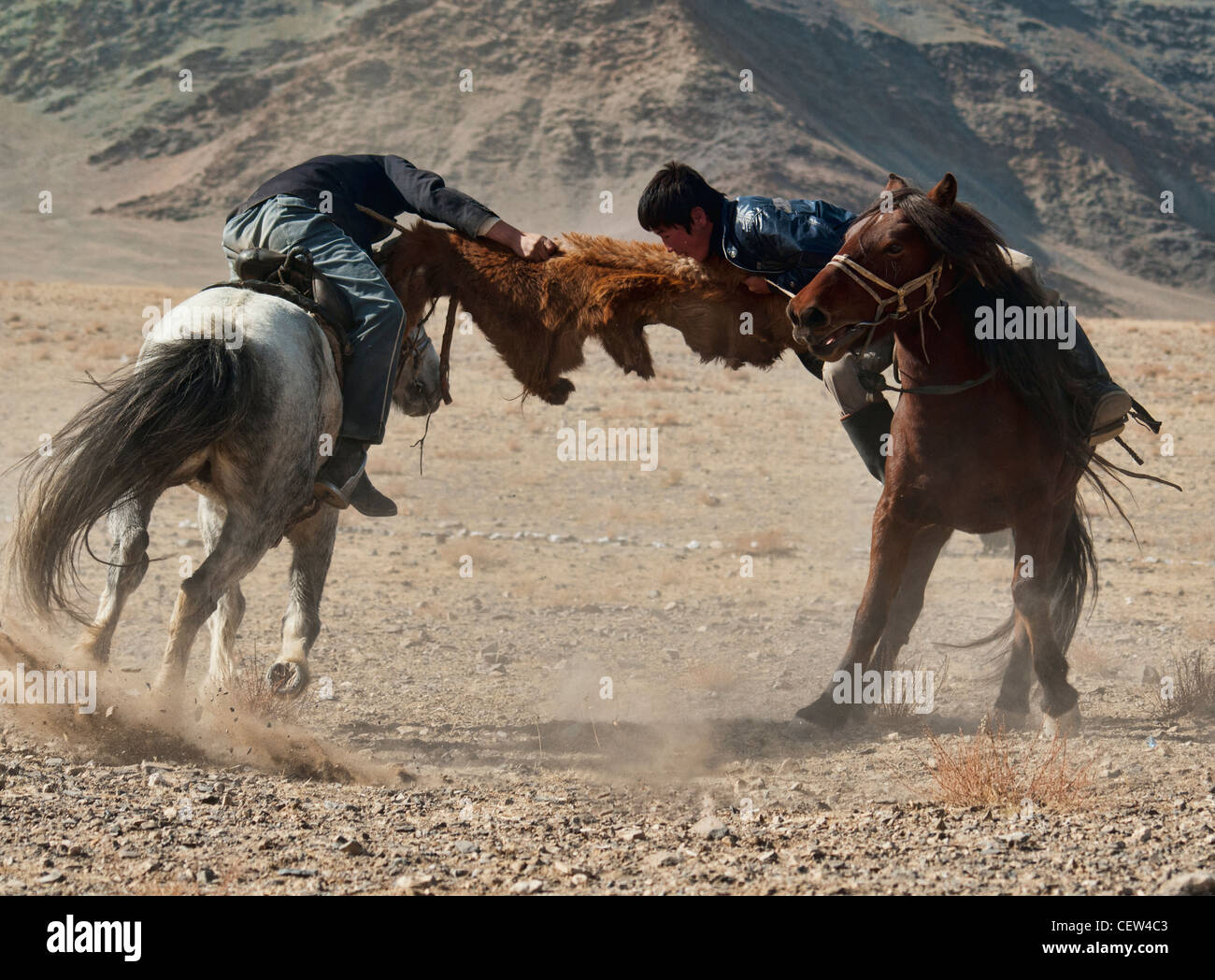 Kazakhs playing kokbar, a traditional sport in which tug of war over a fox or goat pelt is played on horseback, Stock Photo