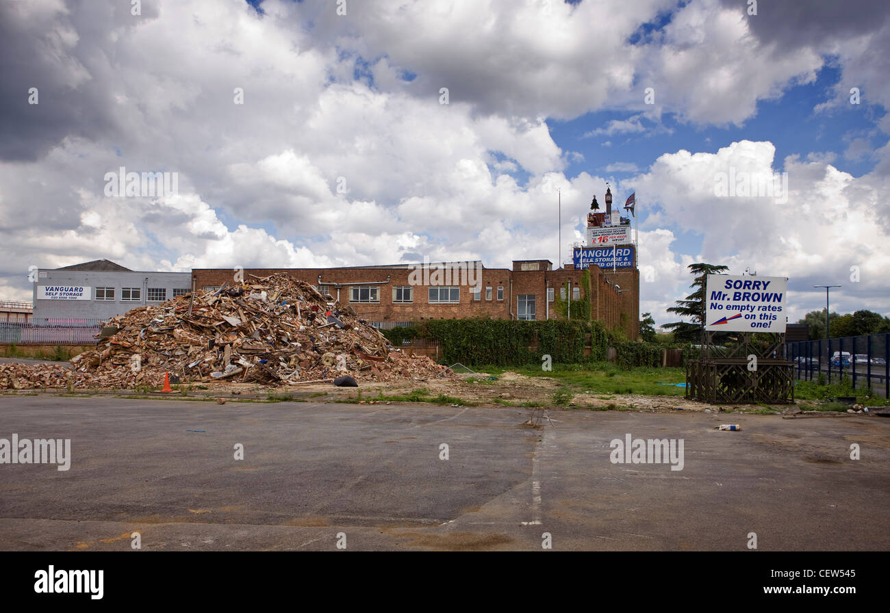 Demolished factory, with sign taunting the government and the prime minister because of avoiding building tax - Stock Image