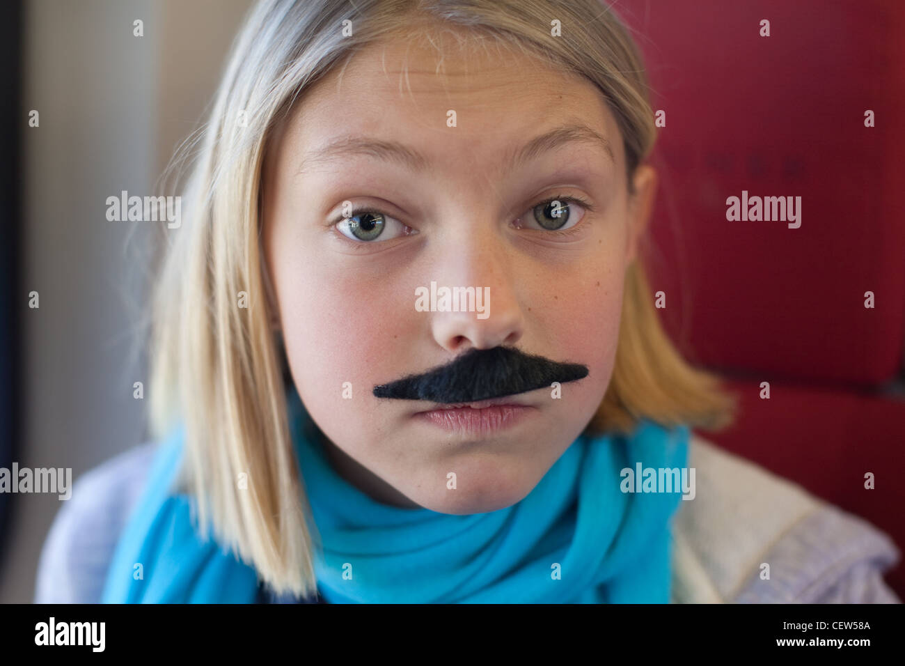 Girl with fake mustache making a silly face - Stock Image
