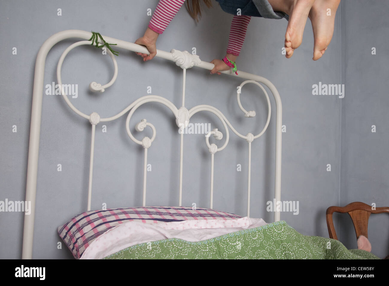 Child jumping on bed, showing only hands holding on and tips of toes, at home in bedroom. - Stock Image