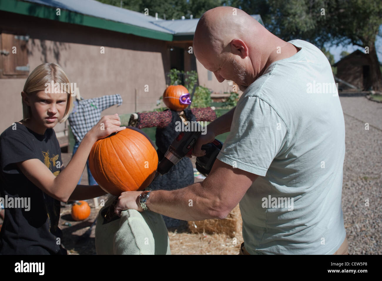 Father and daughter working on making scare crow with pumpkin. - Stock Image