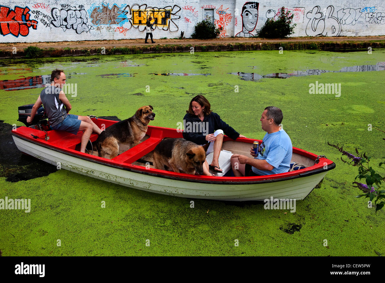 Friends and dogs on a boat trip on the river lea, Hackney Wick, London - Stock Image