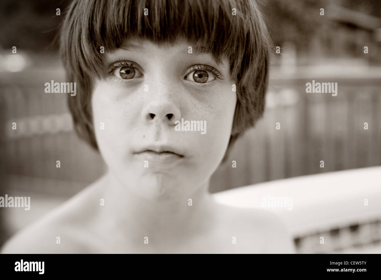 Eight year old boy looking serious, eye contact with camera, outdoors near swimming pool. Stock Photo