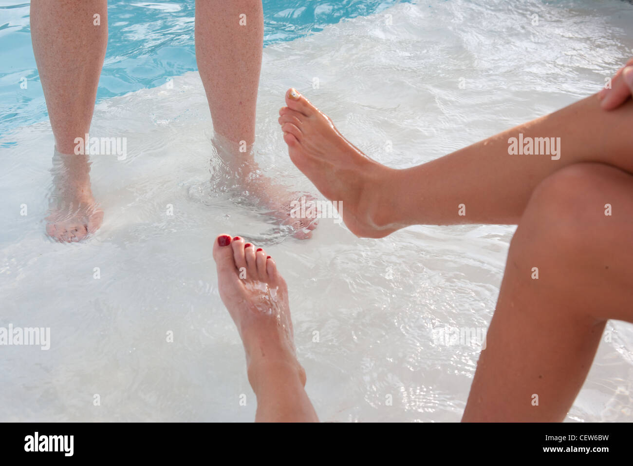 Legs And Feet In And Near Swimming Pool Water Three People Enjoying