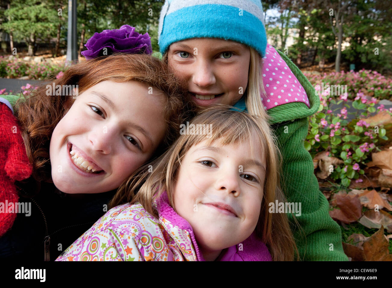 Portrait of three school age girls dressed in winter coats smiling - Stock Image