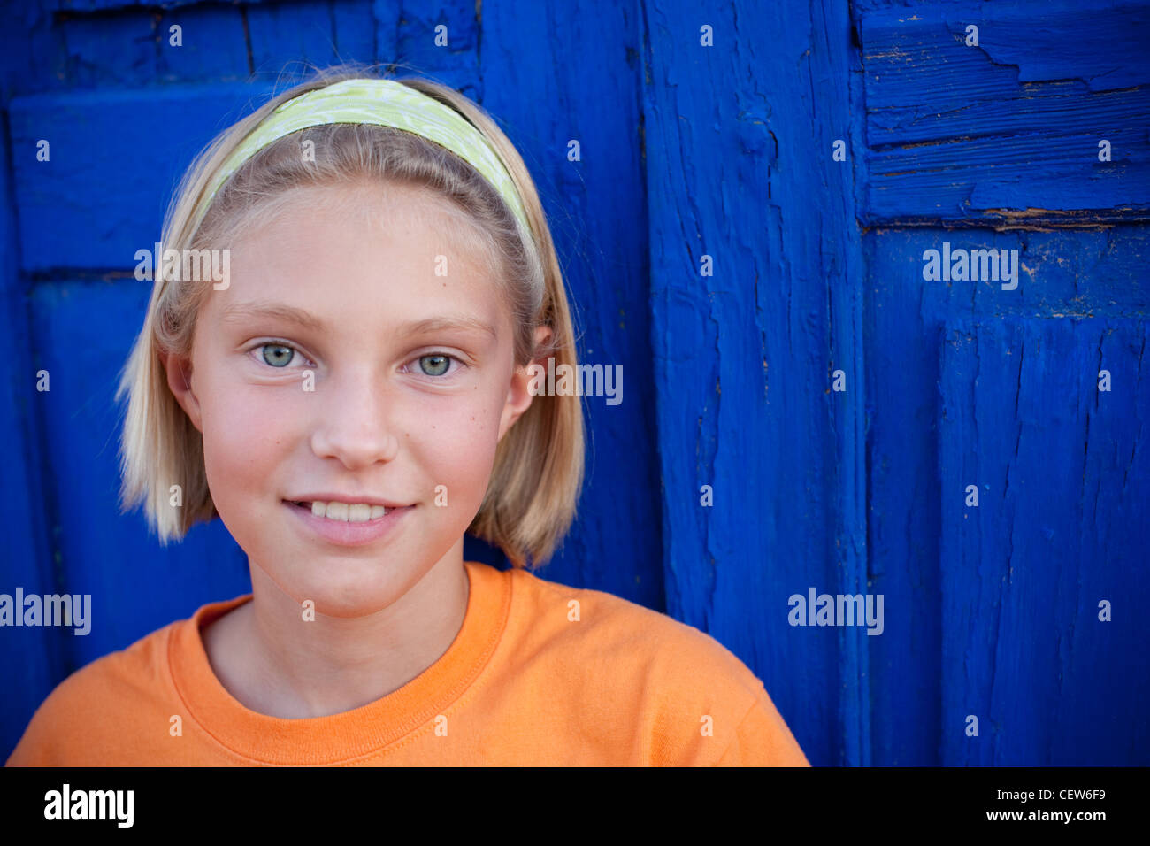 Nine year old girl wearing a headband stands in front of bright blue door smiling. - Stock Image