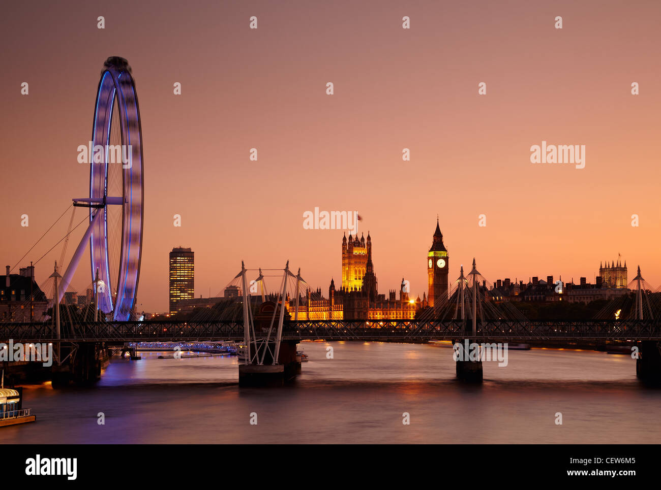 The view along the River Thames of the Millennium Wheel (London Eye), Houses of Parliament and Big Ben at sunset, - Stock Image
