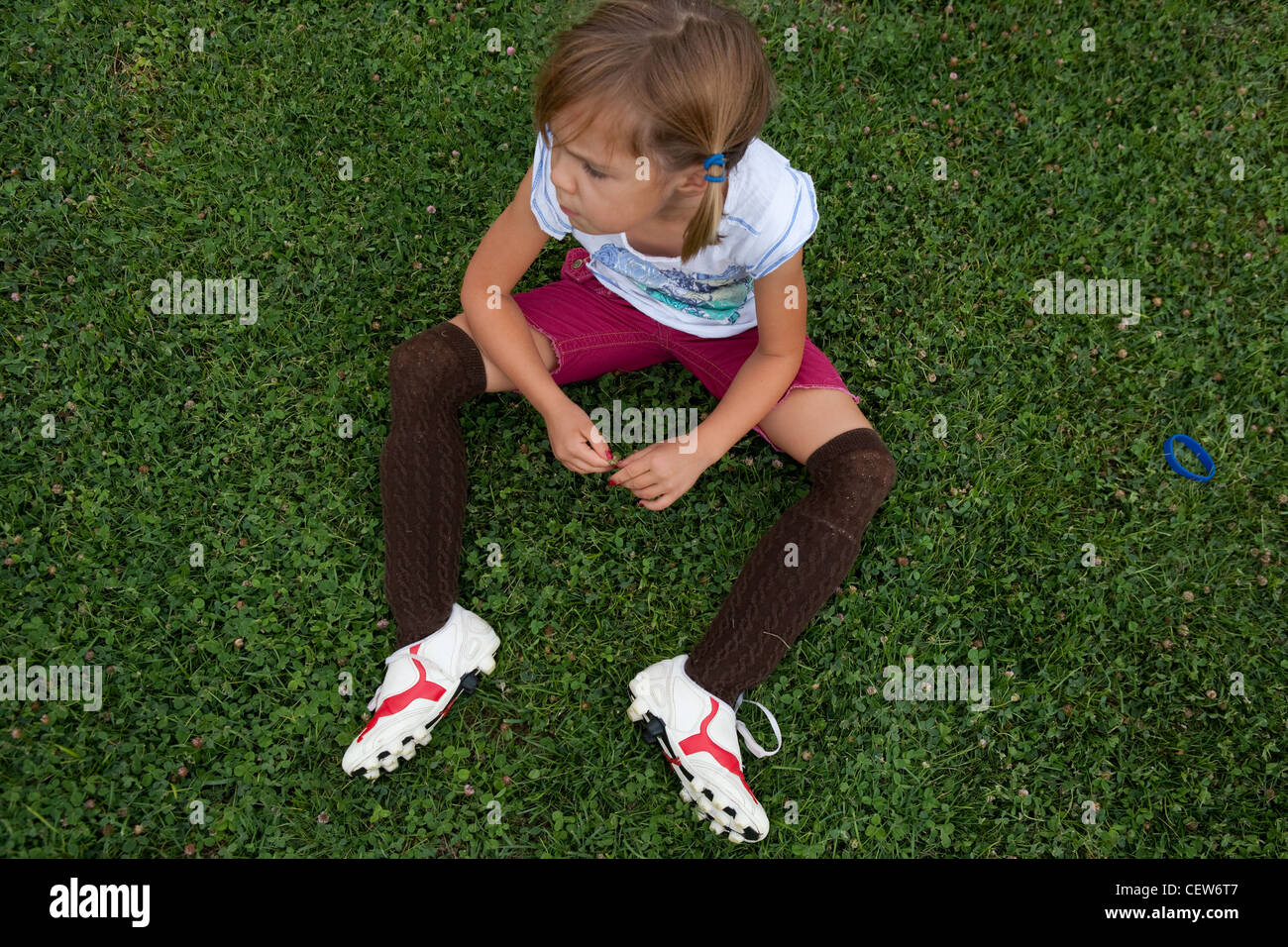 Six year old girl sitting in grass wearing soccer cleat and shin guards. 0dcbf738947a