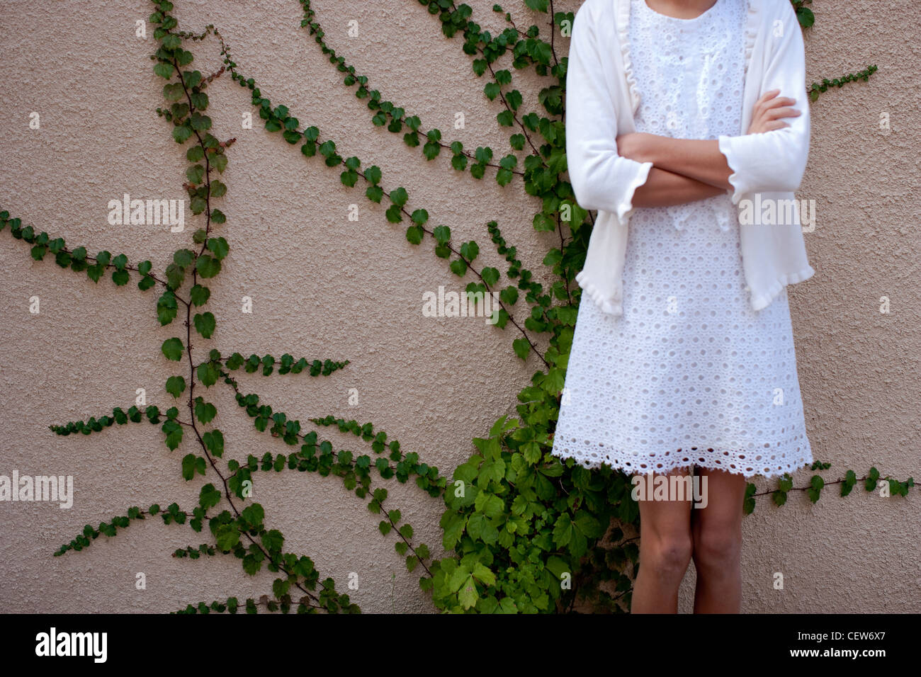 Girl dressed in white in front of climbing vines. - Stock Image