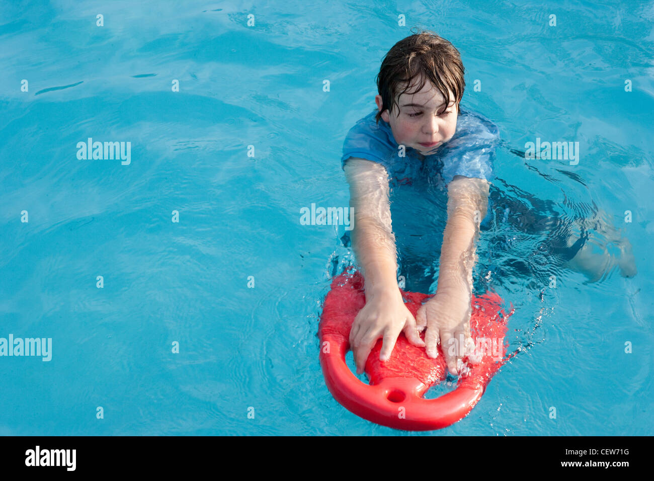 Twelve year old boy floats in swimming pool with a red floatation device. - Stock Image