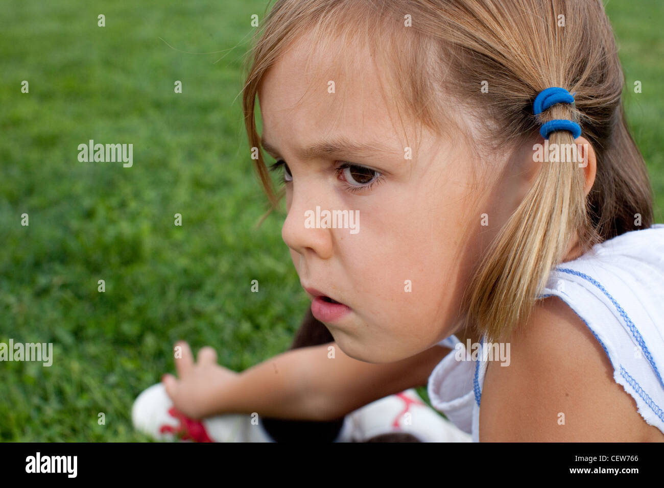 six year old girl sitting in the grass looking serious - Stock Image