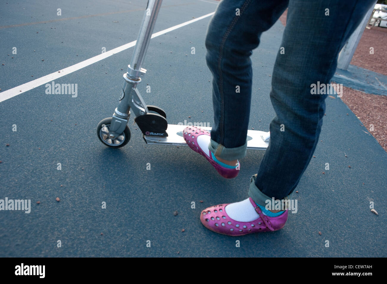 Girl wearing pink sandals riding a scooter Stock Photo