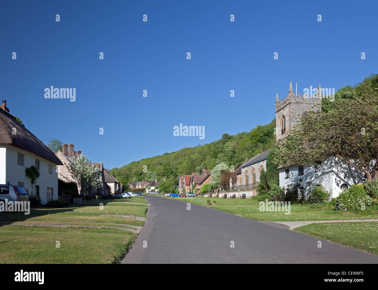 The Street with Thatched Cottages and St. James' Church, Milton Abbas, Dorset, England - Stock Image