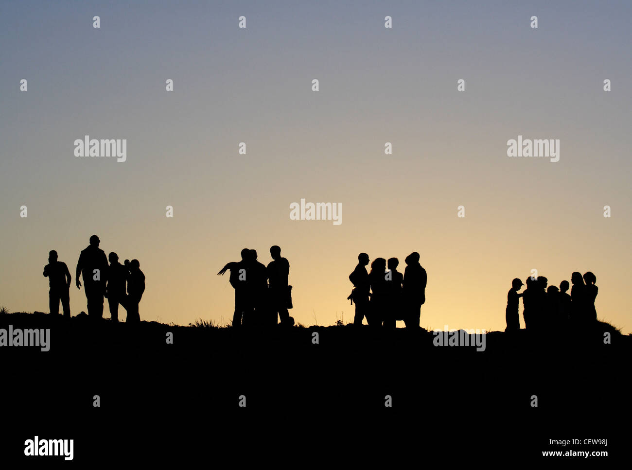 Groups of people in silhouette at dusk. Can be used as lifestyle concept photo illustrating social interaction, - Stock Image