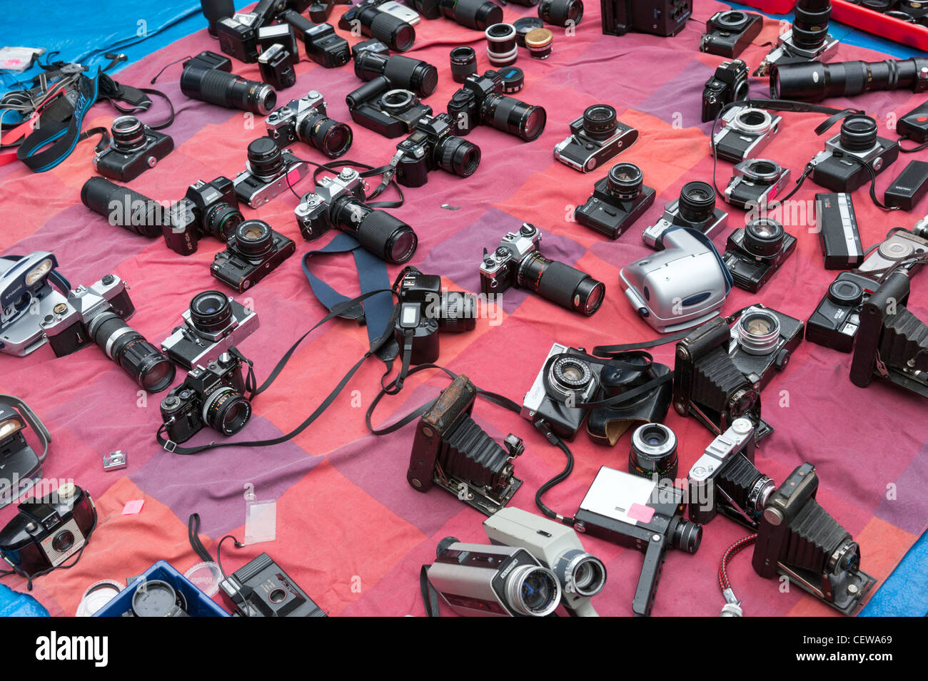 Old secondhand film cameras for sale on market stall in Brick Lane, London, England, UK - Stock Image