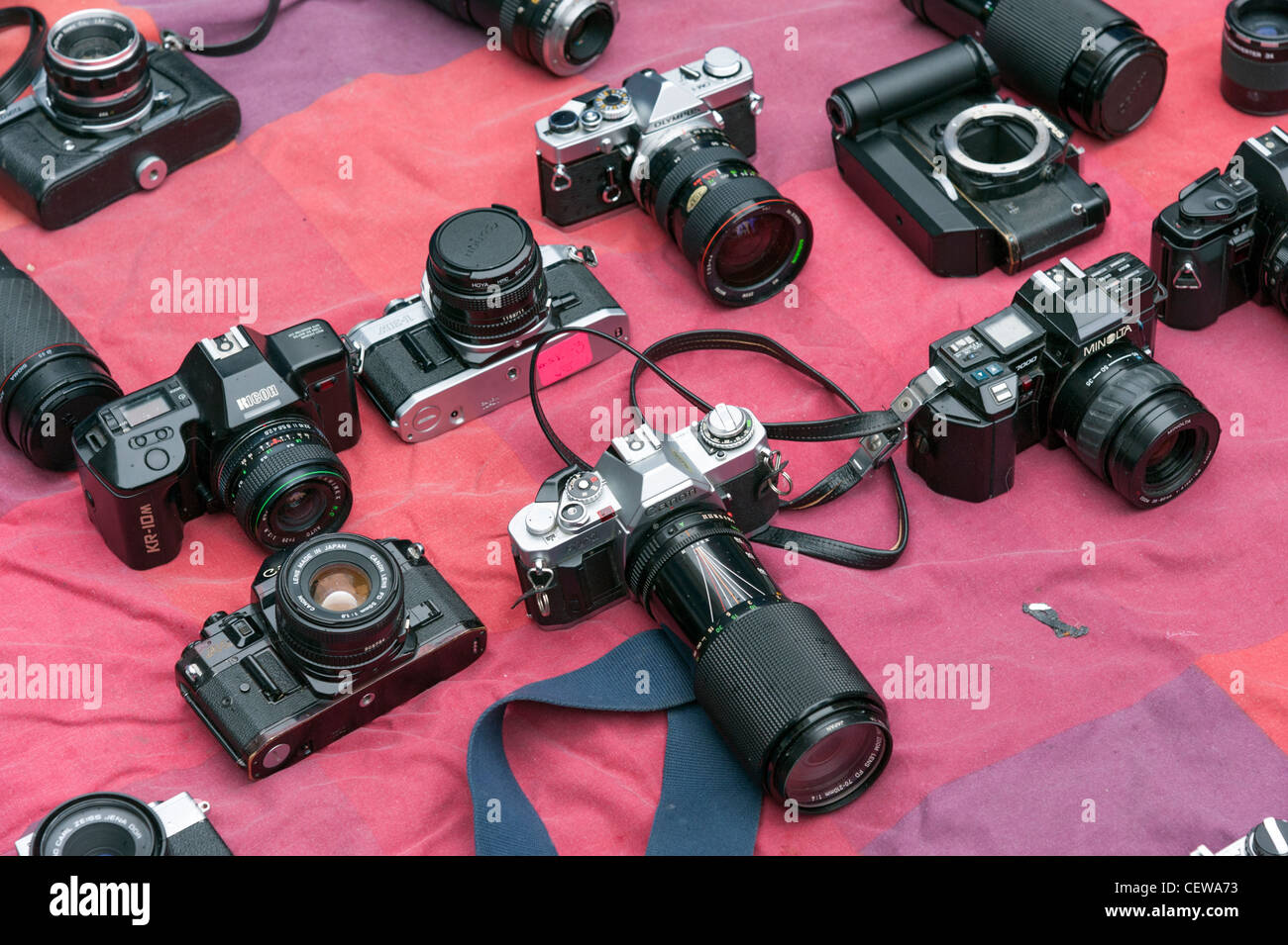 Old secondhand 35mm film cameras for sale on market stall in Brick Lane, London, England, UK - Stock Image