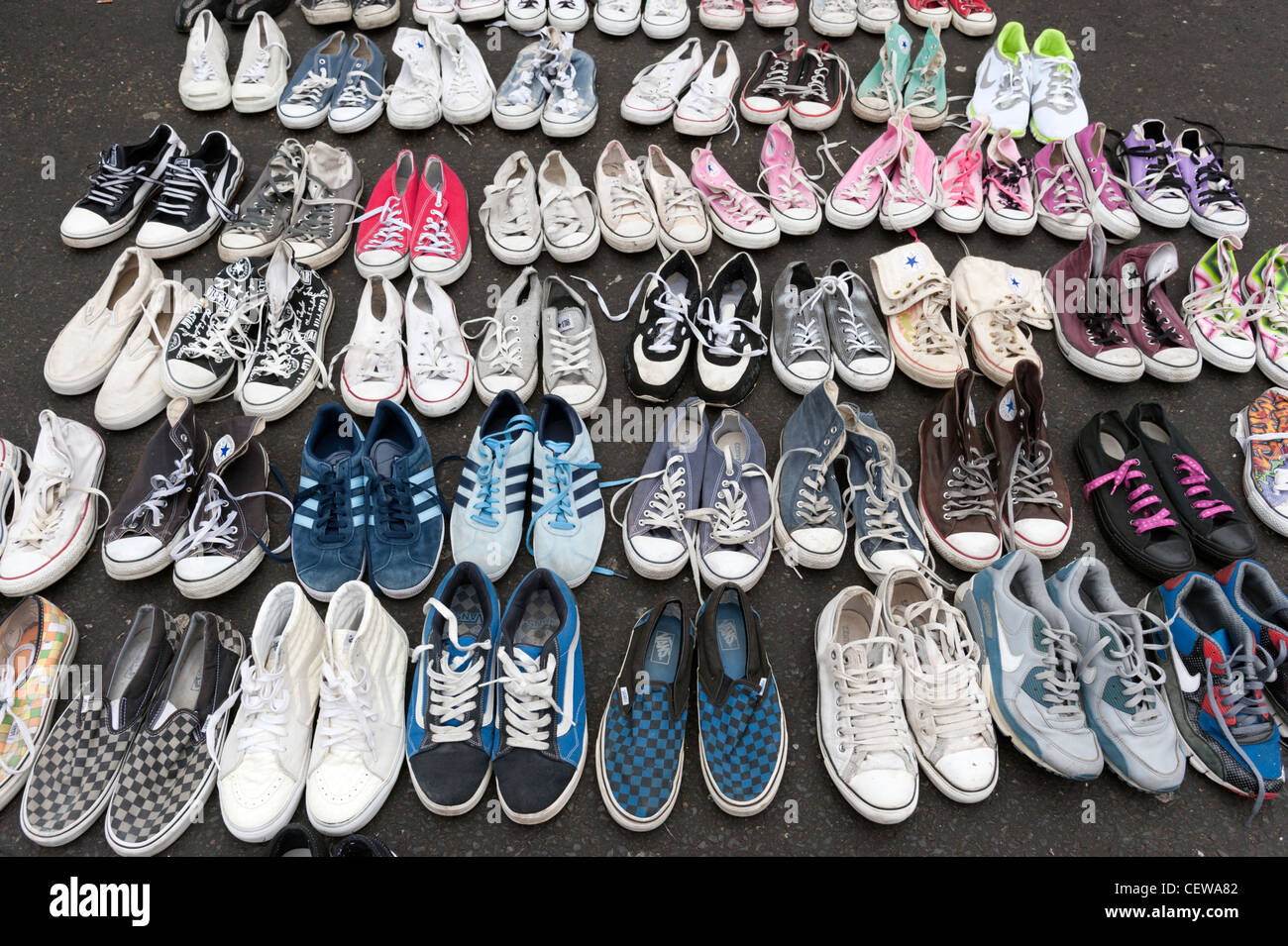 Old secondhand plimsoles for sale on market stall in Brick Lane, London, England, UK - Stock Image