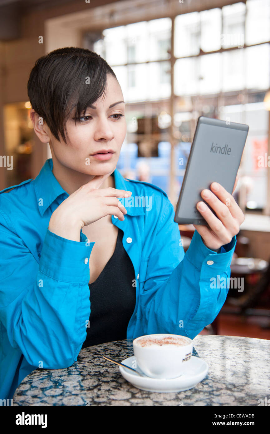 Young woman reading ebook on an Amazon Kindle, UK - Stock Image