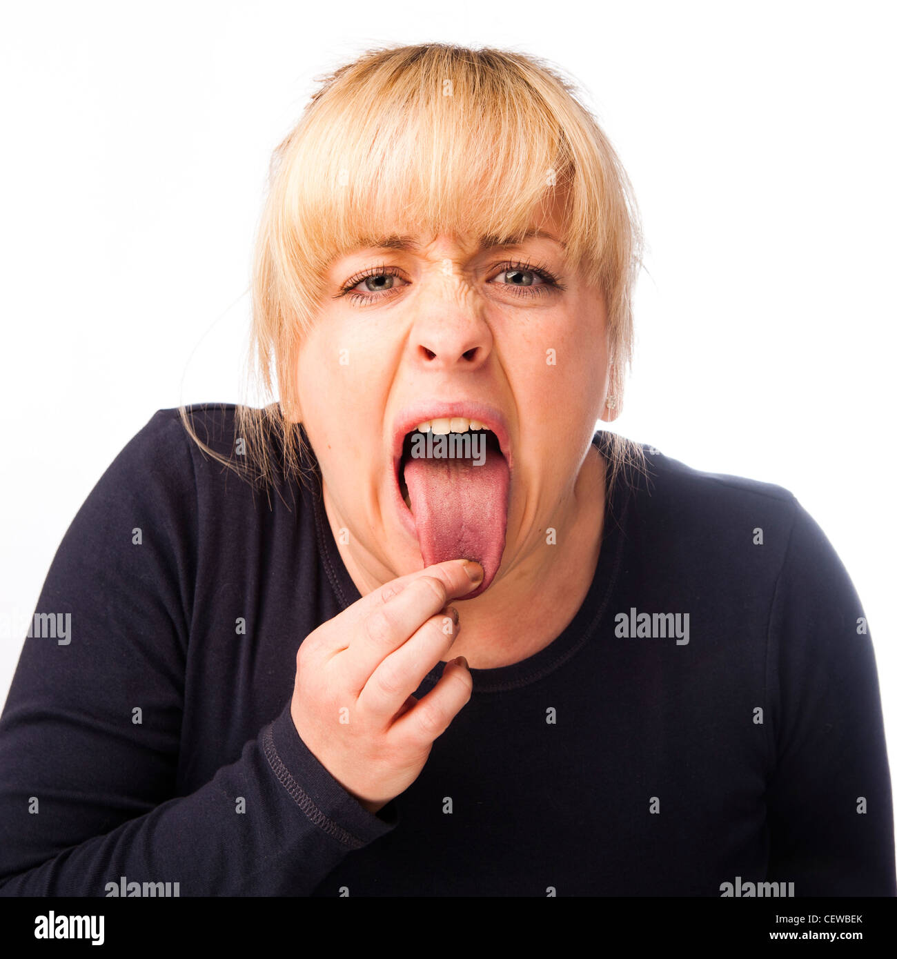 a blonde haired girl woman feeling ill, sticking her tongue out, feeling rough hungover - Stock Image