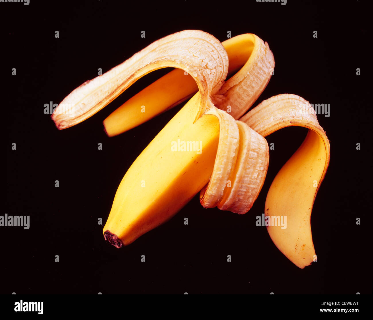 A used banana peel on a black background. - Stock Image