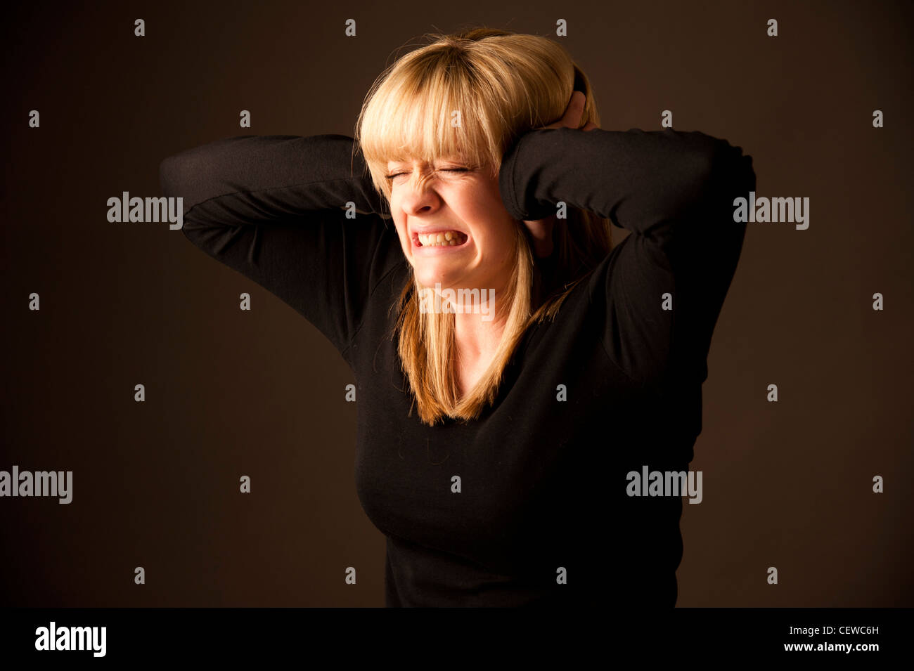 a blonde haired girl woman with her hands over her ears, keeping out the sound - Stock Image