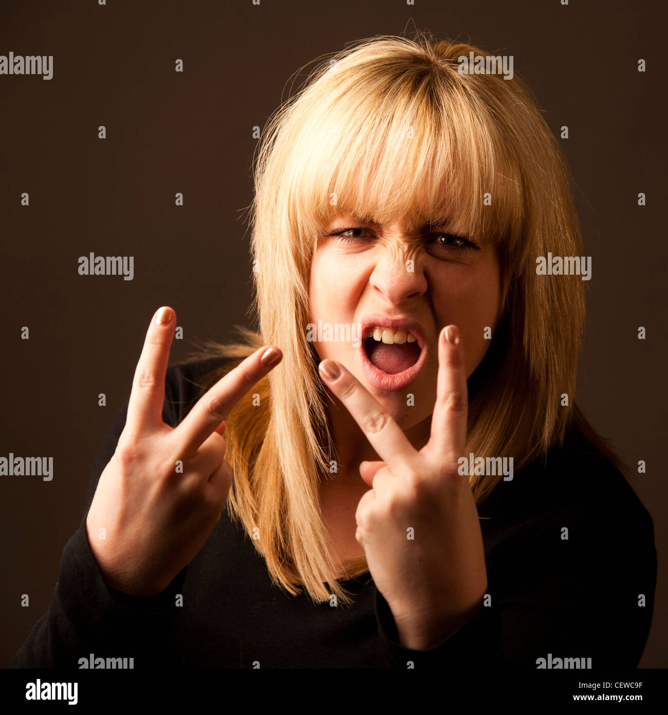 a blonde haired girl woman making an offensive gesture with the fingers of her hand - flicking the v's - Stock Image
