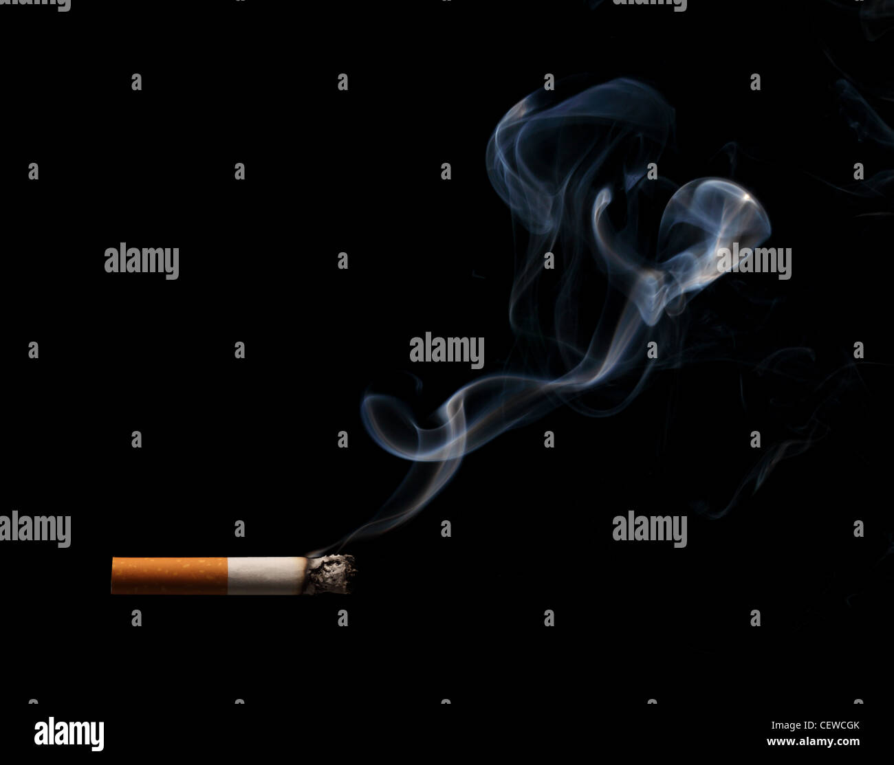 A burning and smoking cigarette on a black background - Stock Image