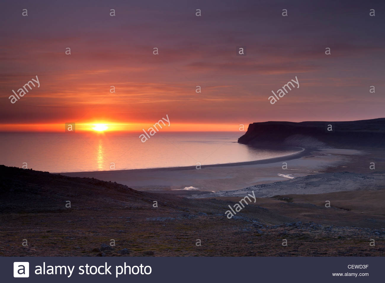 The sun sets over Breiðavik, a small bay that empties into the Altantic Ocean in western Iceland. - Stock Image