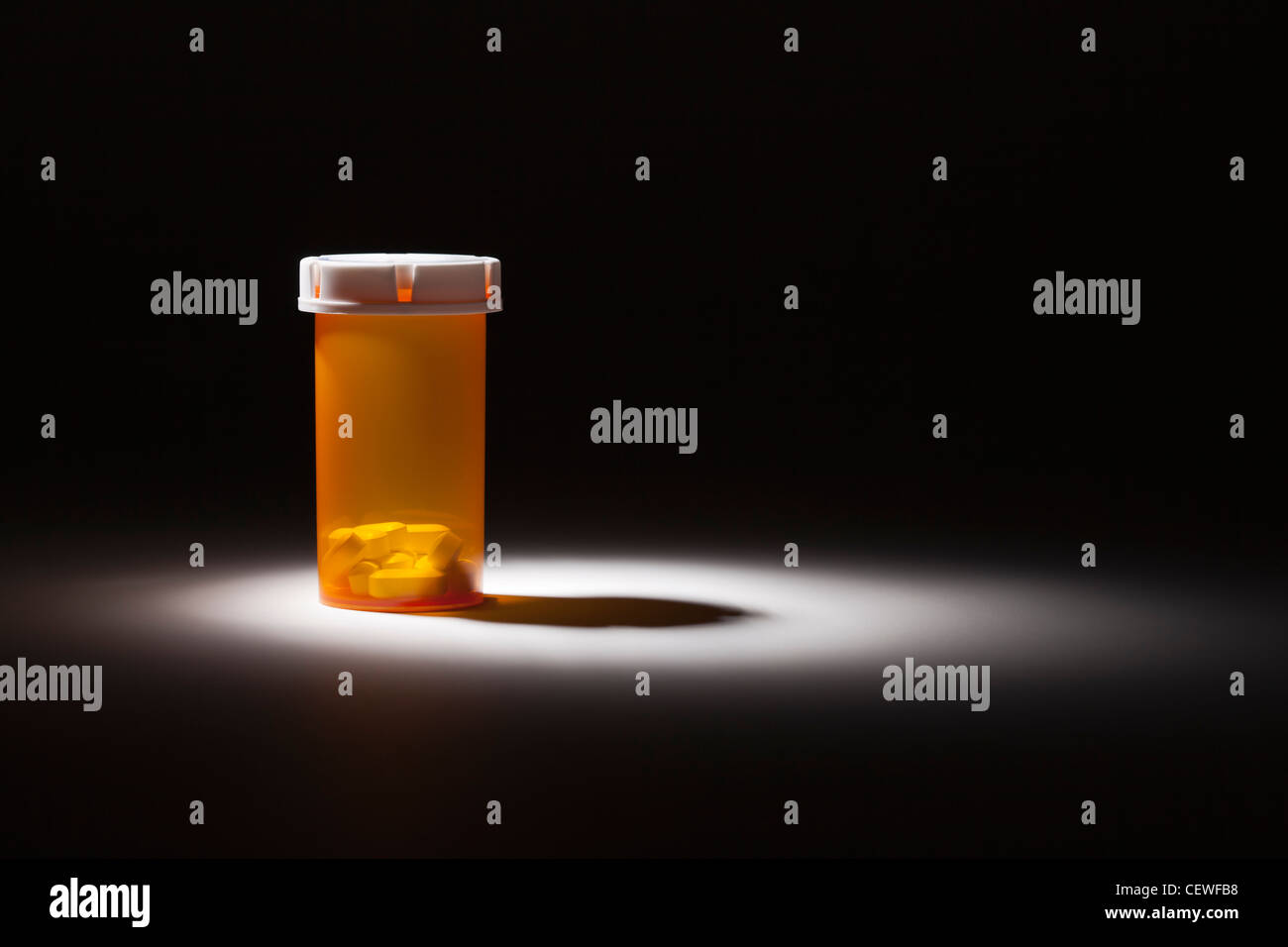Medicine Bottle and Pills Under Spot Light Abstract. - Stock Image