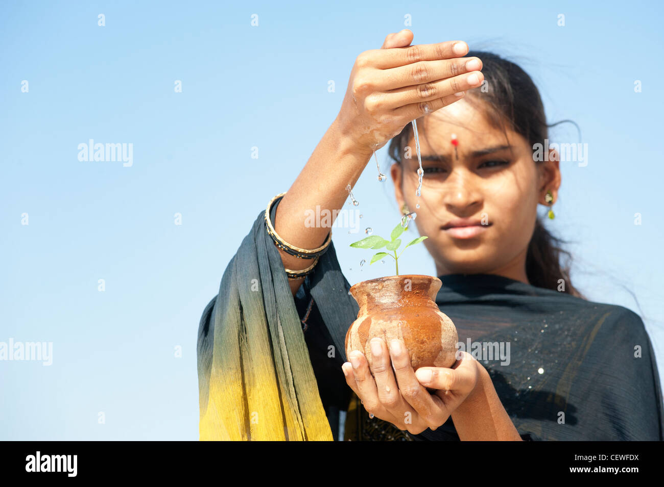 Indian teenage girl sprinkling water over a plant seedling in a clay pot. India Stock Photo